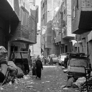 Mokattam Zabbaleen, mulher e filha a percorrer uma uma rua cheia de lixo