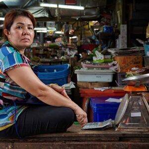 Tailândia, mulher e grande balança no mercado de Samut Songkhram